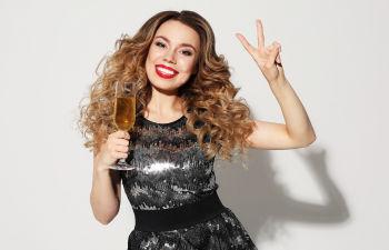 Young stylish woman drinking champagne, celebrating new year, wearing evening dress.