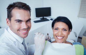 a dentist and a woman patient in a dental chair