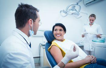 woman in a dental chair talking to a dentist