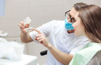dentist showing dentures to a female patient