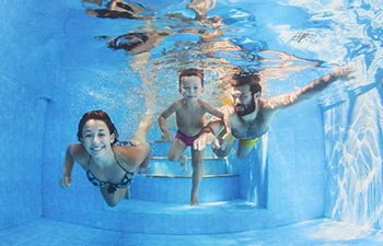 Happy family - father and mother with baby boy swimming and diving underwater with fun in blue pool.