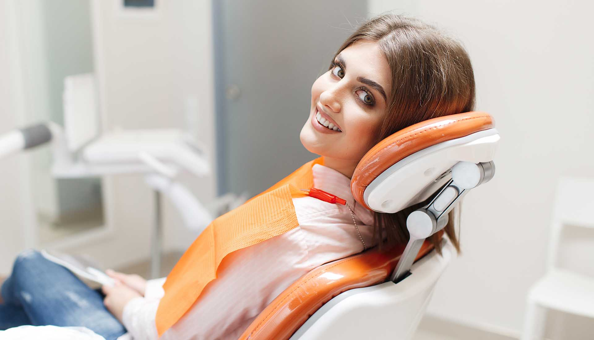 happy young woman in a dental chair after dental checkup and cleaning