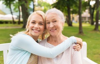 happy young woman hugging her smiling grandmother sitting on a bench in a park