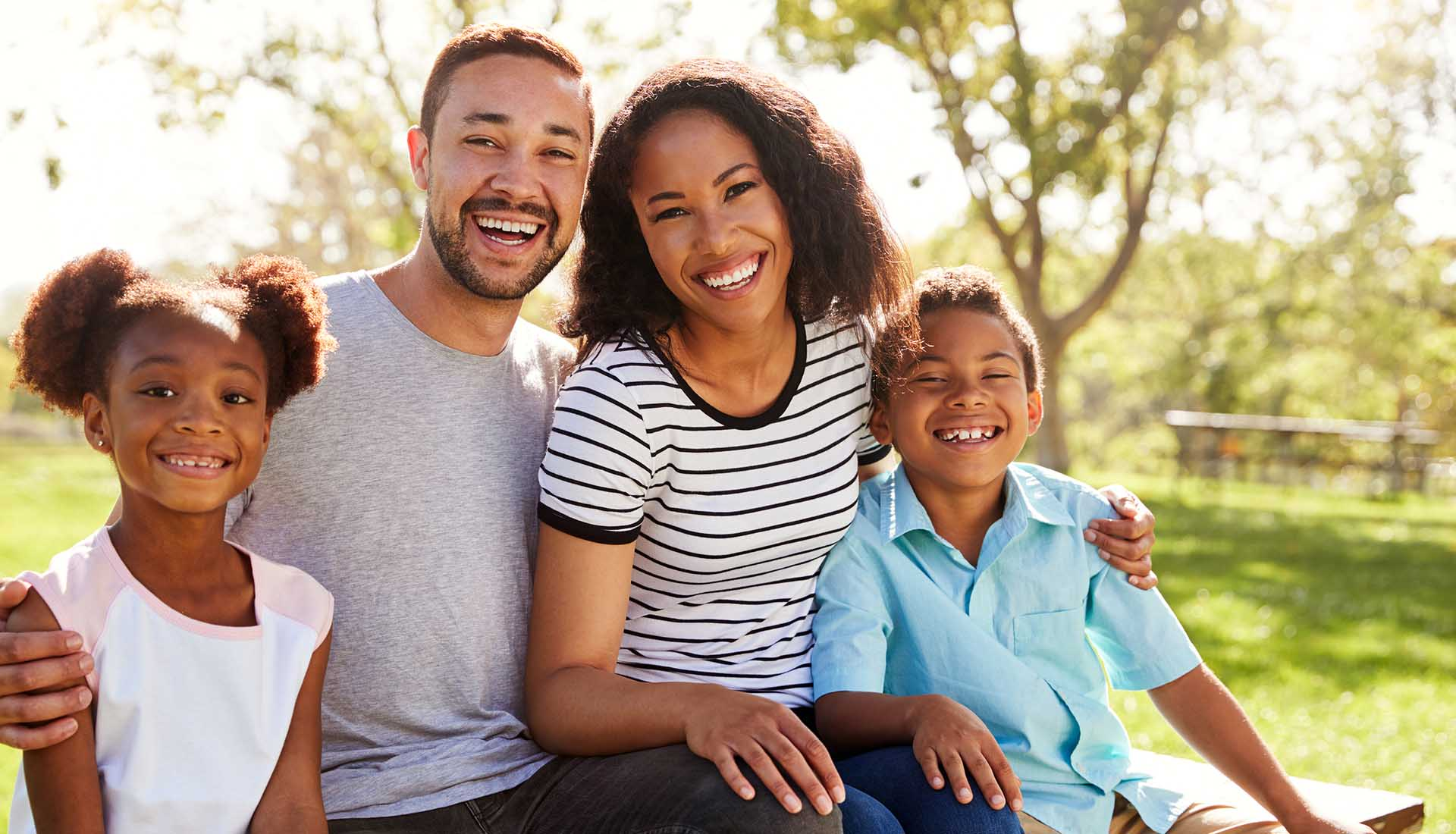 happy Afro-American family of four spending time outdoors
