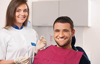 Happy male patient and smiling female dentist at dental surgery.