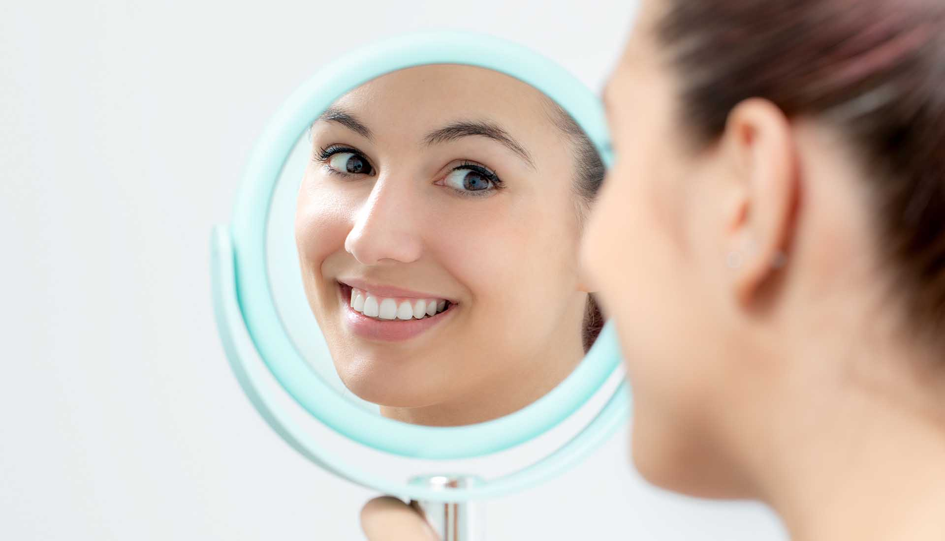 young woman looking at her perfect teeth in a mirror