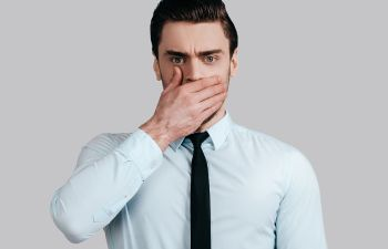 Man covering his mouth with his hand due to bad breath