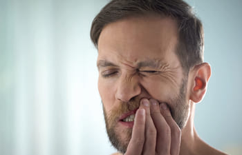 man with dental pain caused by gum disease